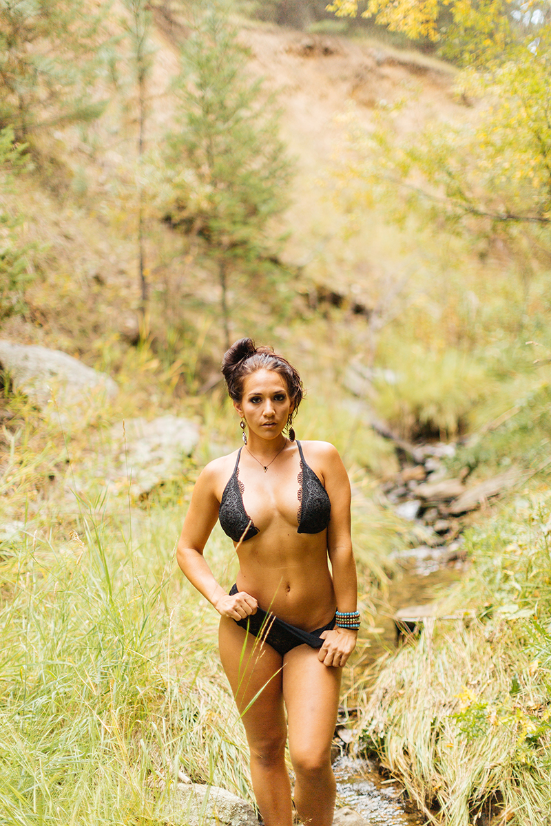 A beautiful young brunette woman poses for a Genesee Park boudoir photos session near Denver, Colorado in the Rocky Mountains wearing a black bra and black underwear set in a field near a creek
