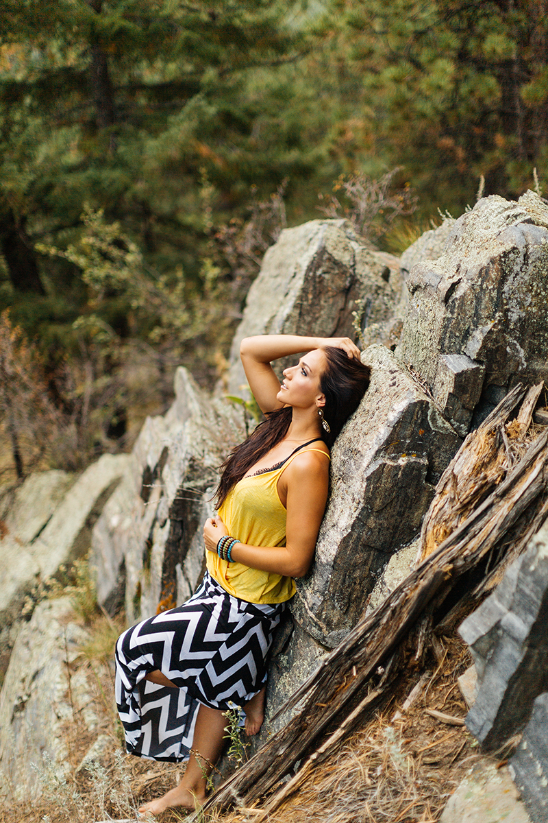 A beautiful young brunette woman poses for a Genesee Park boudoir photos session near Denver, Colorado in the Rocky Mountains wearing a yellow shirt with a black and white chevron pattern skirt leaning against a bunch of stone