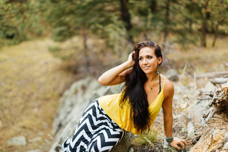 A beautiful young brunette woman poses for a Genesee Park boudoir photos session near Denver, Colorado in the Rocky Mountains wearing a yellow shirt with a black and white chevron pattern skirt sitting on stones