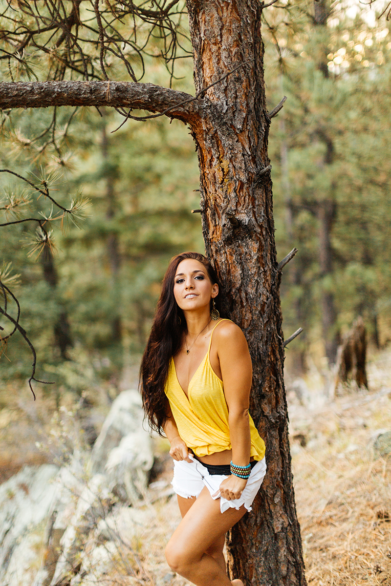 A beautiful young brunette woman poses for a Genesee Park boudoir photos session near Denver, Colorado in the Rocky Mountains wearing a yellow shirt with white shorts leaning against a tree