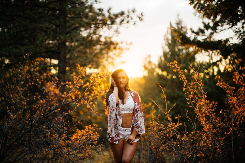 A beautiful young brunette woman poses for a Genesee Park boudoir photos session near Denver, Colorado in the Rocky Mountains wearing a white bra, white underwear and a red and white robe in a field surrounded by trees as the sun sets behind her