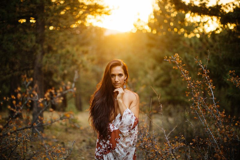 A beautiful young brunette woman poses topless for a Genesee Park boudoir photos session near Denver, Colorado in the Rocky Mountains wearing white underwear and a red and white robe in a field surrounded by trees as the sun sets behind her