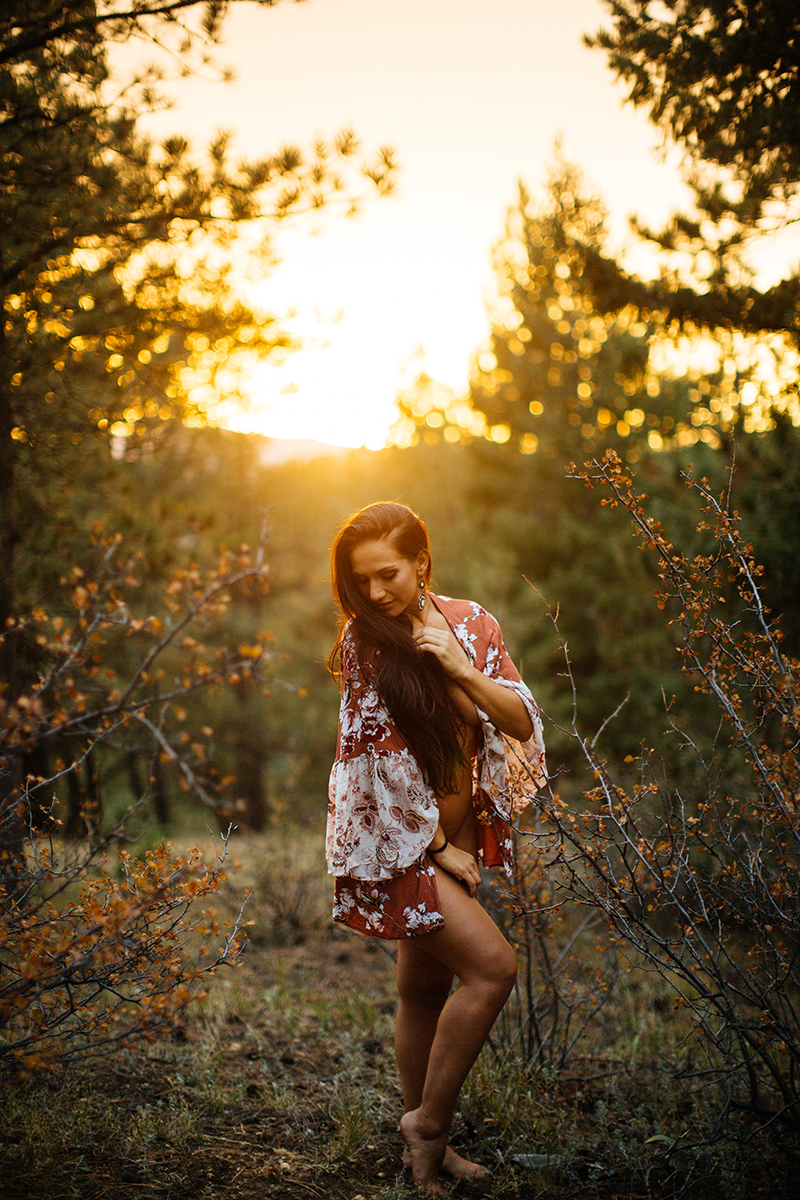 A beautiful young brunette woman poses nude for a Genesee Park boudoir photos session near Denver, Colorado in the Rocky Mountains wearing a red and white robe in a field surrounded by trees as the sun sets behind her