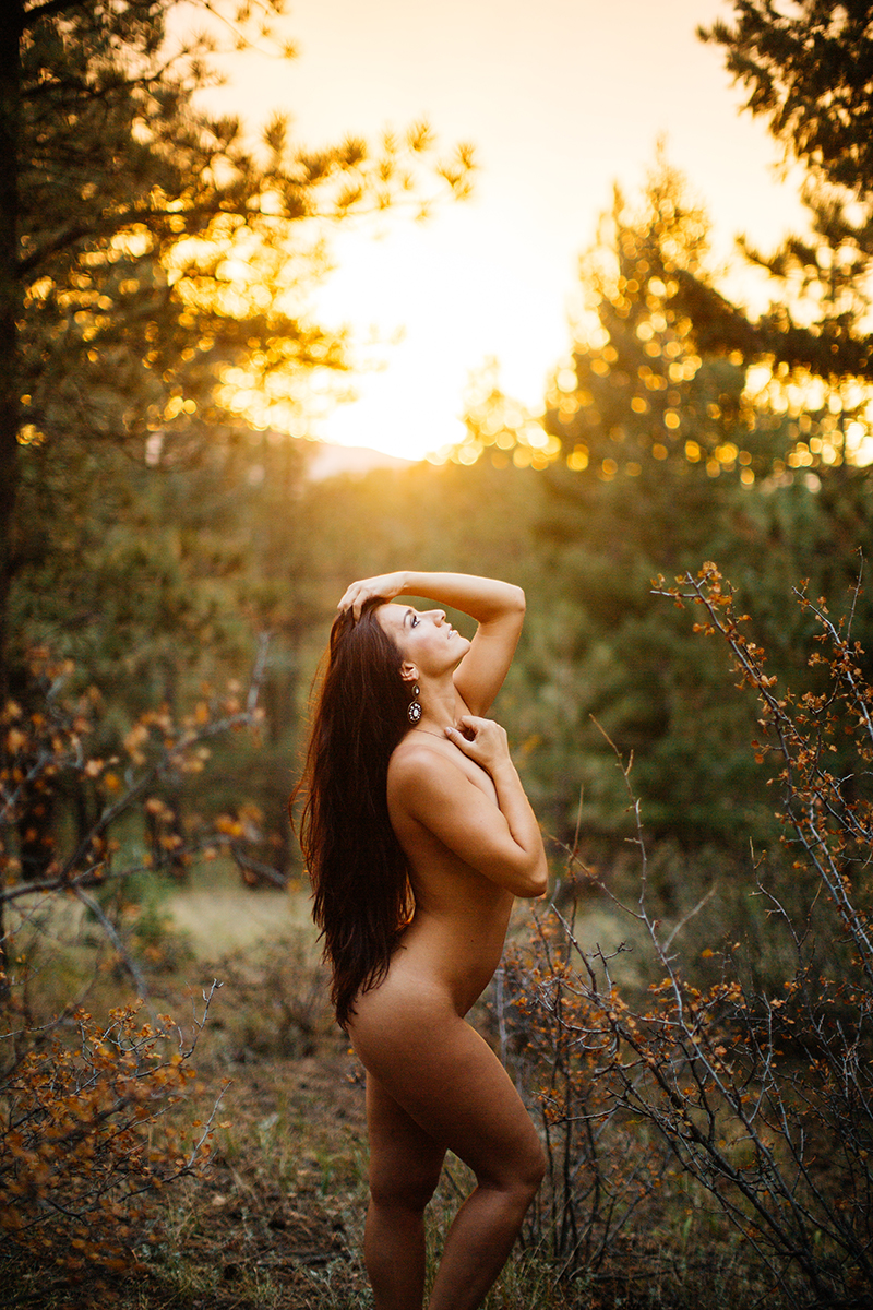 A beautiful young brunette woman poses nude for a Genesee Park boudoir photos session near Denver, Colorado in the Rocky Mountains in a field surrounded by trees as the sun sets behind her