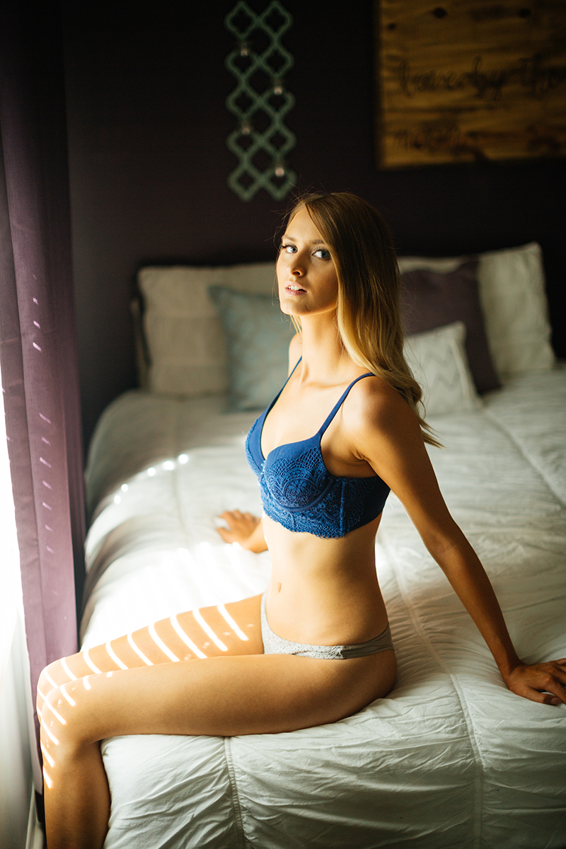 A beautiful young blonde woman poses for some Thornton boudoir photos near Denver, Colorado wearing a blue bra and white underwear sitting on a white bed in front of a window