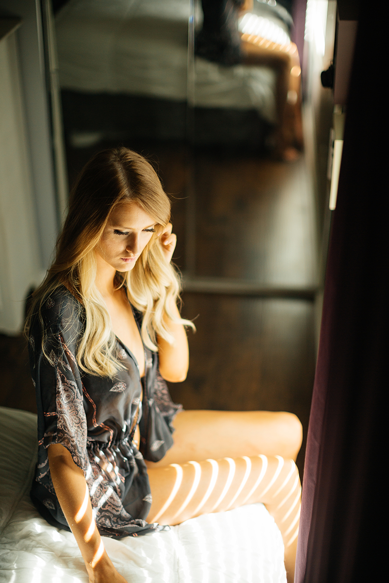 A beautiful young blonde woman poses topless for some Thornton boudoir photos near Denver, Colorado wearing white underwear and a silk robe sitting on a white bed in front of a window