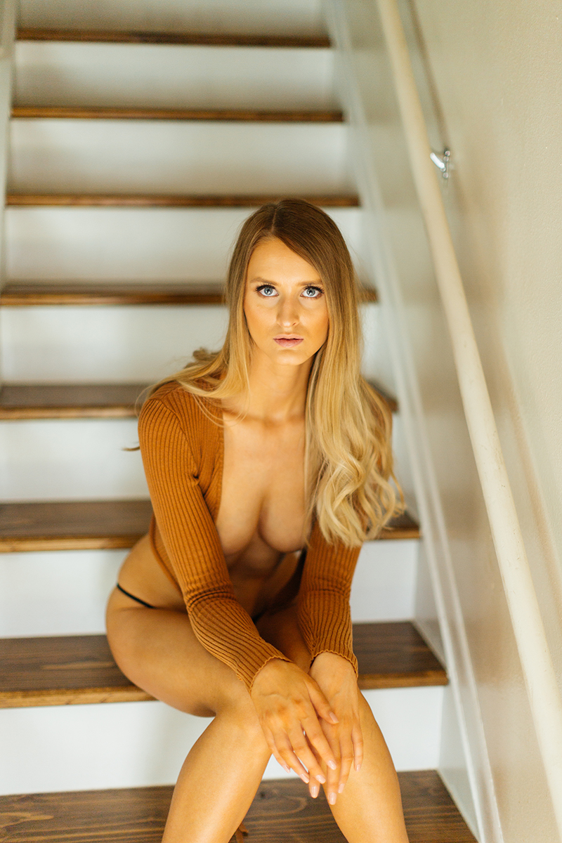A beautiful young blonde woman poses topless for some Thornton boudoir photos near Denver, Colorado wearing black underwear and an orange sweater sitting on wood steps