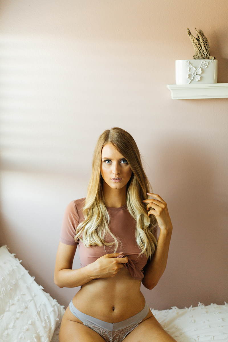 A beautiful young blonde woman poses for some Thornton boudoir photos near Denver, Colorado wearing a tight pink shirt and light blue underwear sitting on a white bed