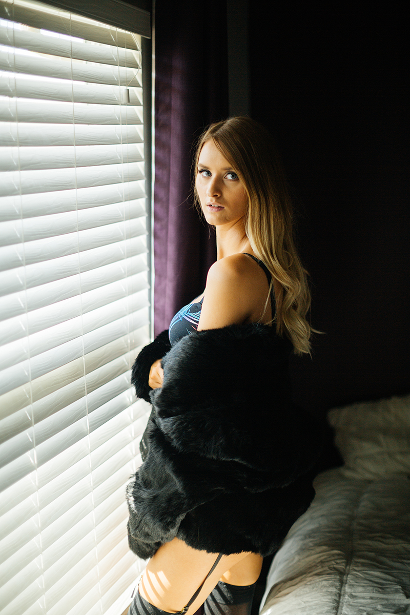 A beautiful young blonde woman poses for some Thornton boudoir photos near Denver, Colorado wearing a black colorful bra, black underwear, a black garter with black stockings and a black fur coat standing in front of a white bed next to a window