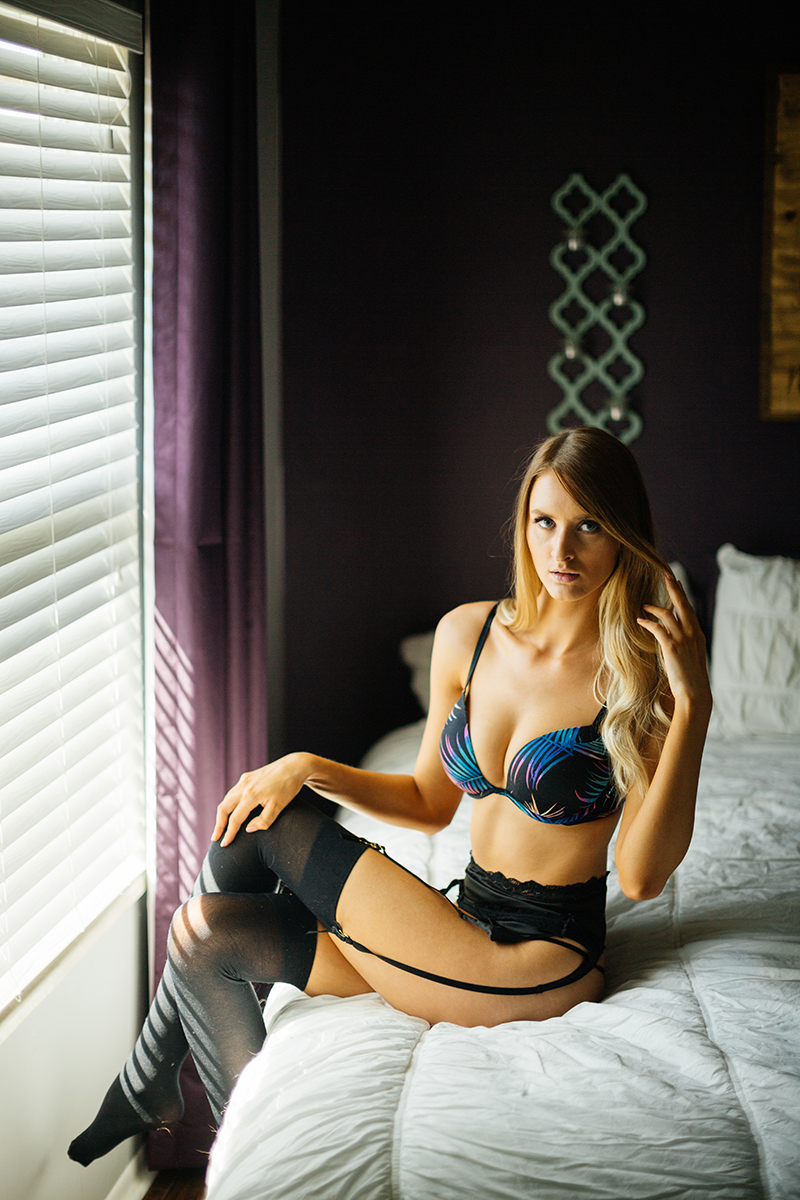 A beautiful young blonde woman poses for some Thornton boudoir photos near Denver, Colorado wearing a black colorful bra, black underwear and a black garter with black stockings sitting on a white bed next to a window