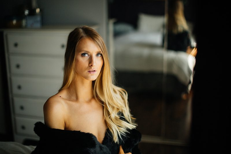 A beautiful young blonde woman poses topless for some Thornton boudoir photos near Denver, Colorado wearing black underwear, a black garter with black stockings and a black fur coat sitting on a white bed next to a window