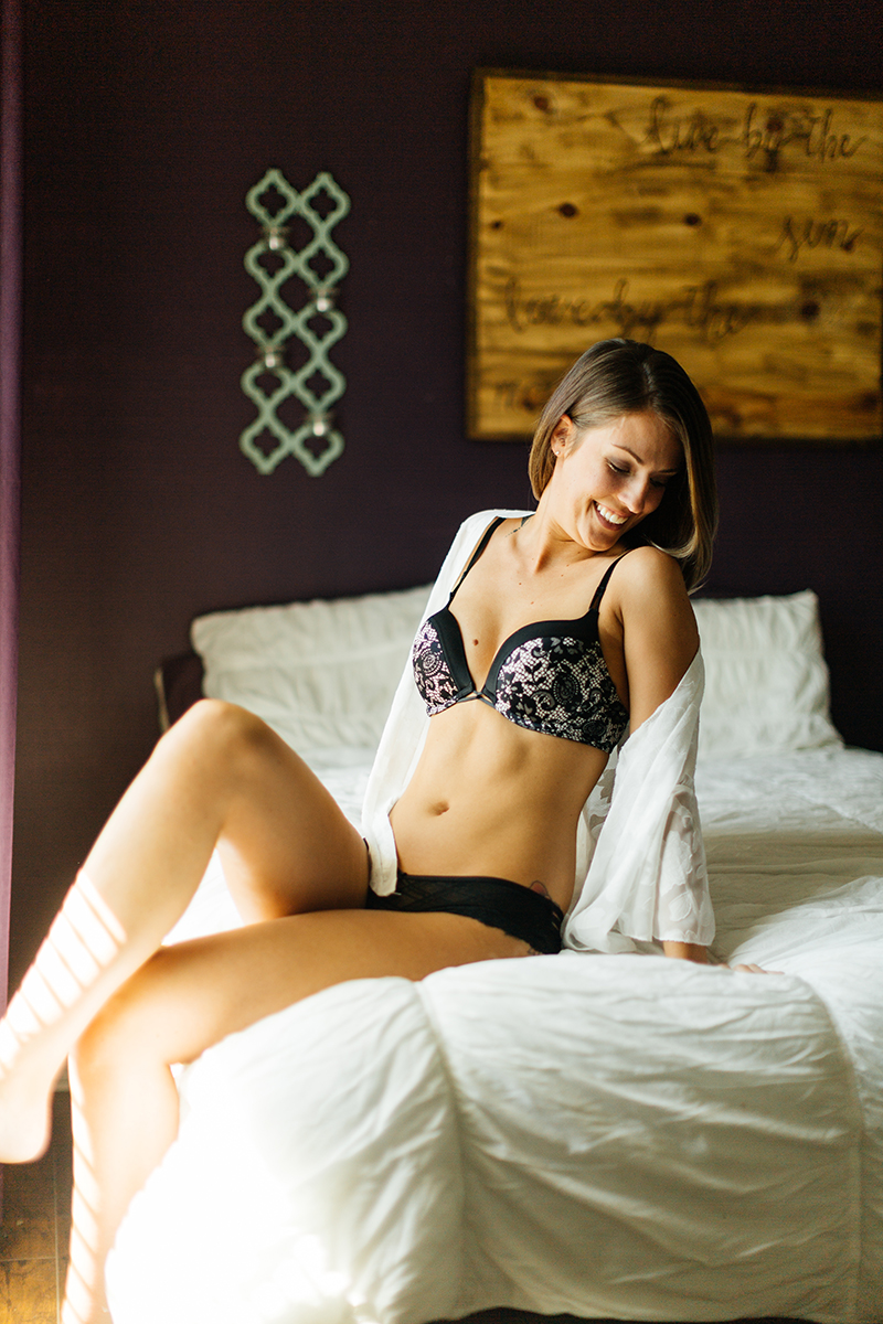 A beautiful young brunette woman poses for a Thornton boudoir studio photography session near Denver, Colorado wearing a black bra, black underwear and a white button up shirt sitting on a white bed near a window