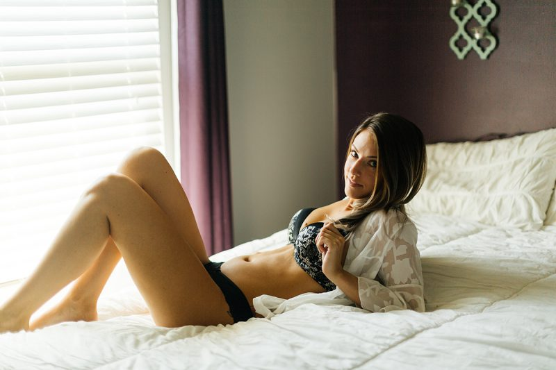 A beautiful young brunette woman poses for a Thornton boudoir studio photography session near Denver, Colorado wearing a black bra, black underwear and a white button up shirt laying on a white bed near a window