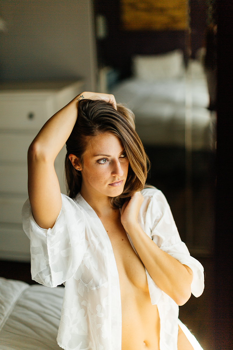A beautiful young brunette woman poses topless for a Thornton boudoir studio photography session near Denver, Colorado wearing black underwear and a white button up shirt sitting on a white in front of a mirror