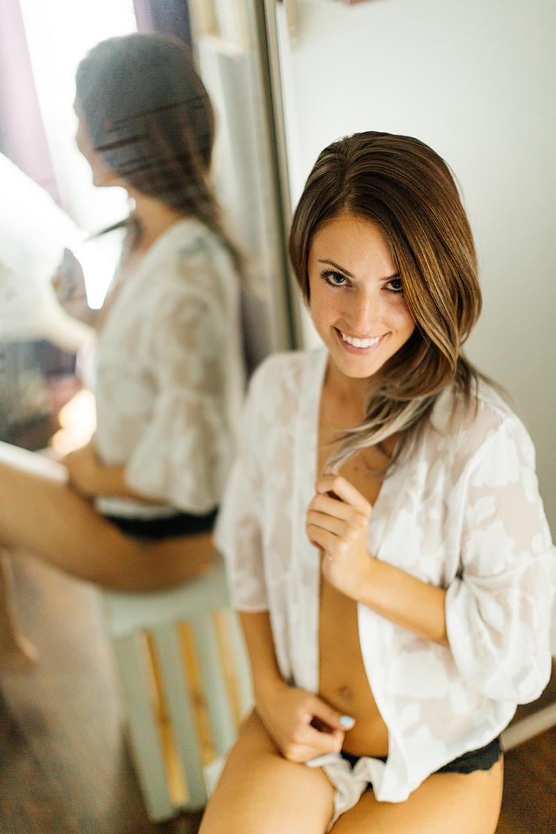 A beautiful young brunette woman poses topless for a Thornton boudoir studio photography session near Denver, Colorado wearing black underwear and a white button up shirt standing in front of a mirror