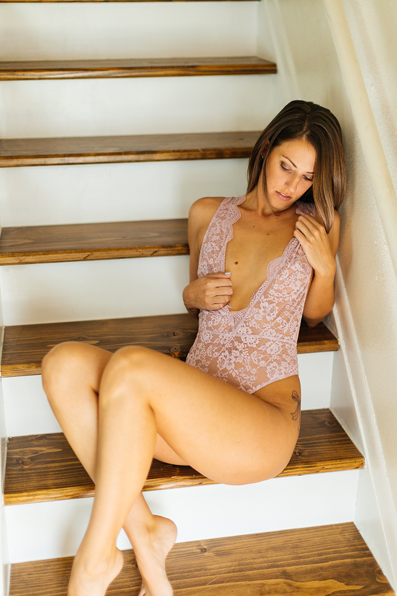 A beautiful young brunette woman poses for a Thornton boudoir studio photography session near Denver, Colorado wearing purple lingerie on wood stairs