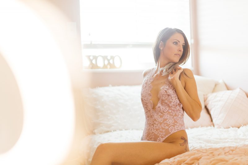 A beautiful young brunette woman poses for a Thornton boudoir studio photography session near Denver, Colorado wearing purple lingerie on a white bed