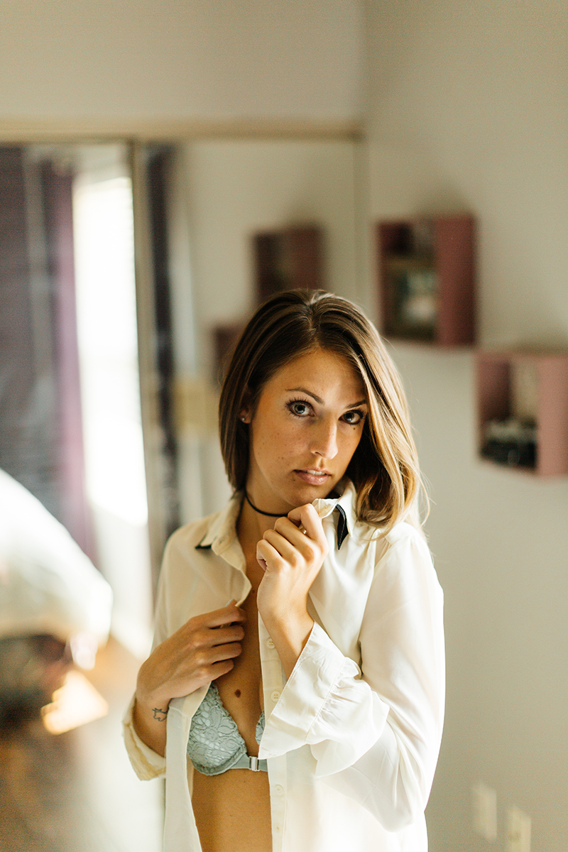 A beautiful young brunette woman poses for a Thornton boudoir studio photography session near Denver, Colorado wearing a teal bra and underwear set and a white button up shirt in front of a mirror