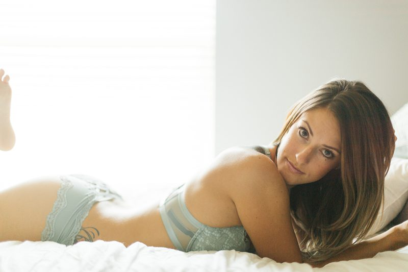 A beautiful young brunette woman poses for a Thornton boudoir studio photography session near Denver, Colorado wearing a teal bra and underwear set laying on a white bed
