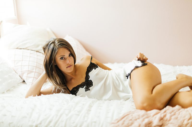 A beautiful young brunette woman poses for a Thornton boudoir studio photography session near Denver, Colorado wearing white lingerie with black lace sitting on a white bed