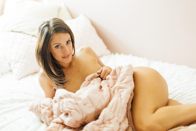 A beautiful young brunette woman poses nude for a Thornton boudoir studio photography session near Denver, Colorado wrapped up in a pink blanket on a white bed