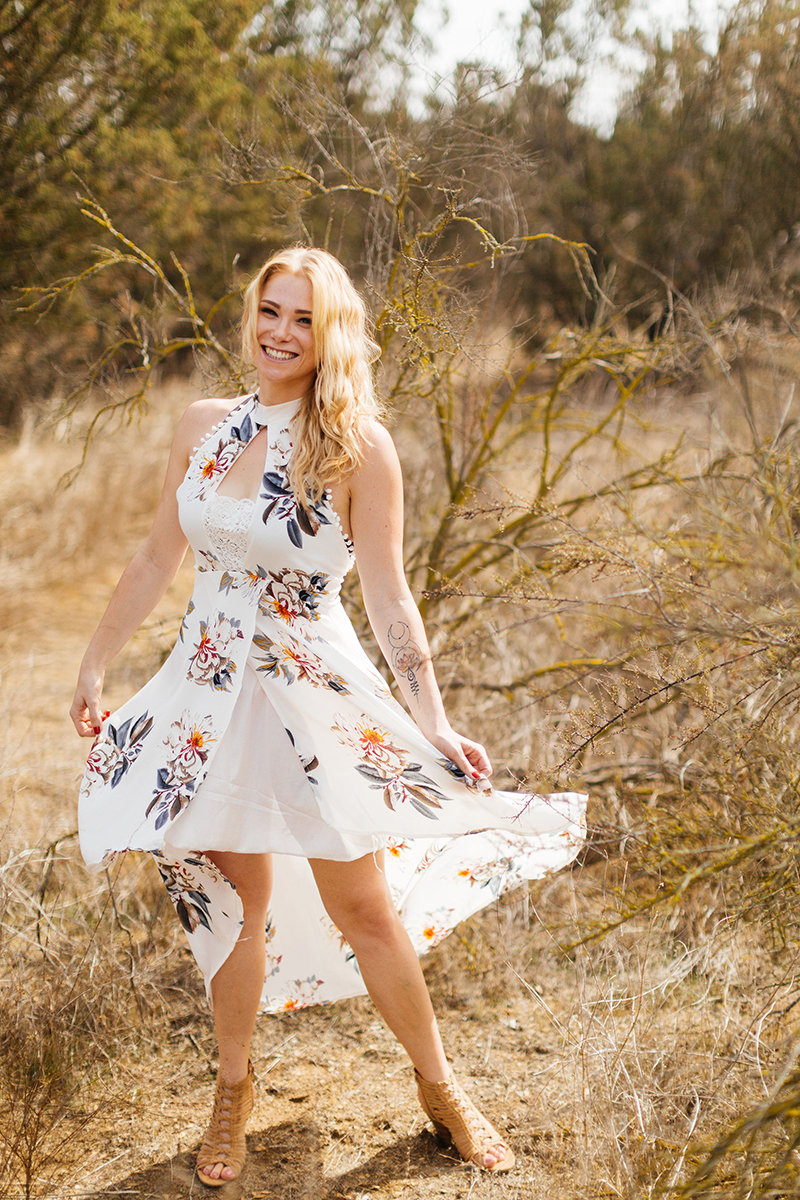 A beautiful young blonde woman twirls her dress for an Estelle Mountain Reserve boudoir photography session in a white floral dress in a dry field in Corona just outside of Los Angeles, California