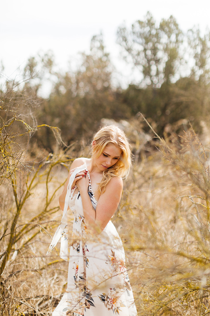 A beautiful young blonde woman poses for an Estelle Mountain Reserve boudoir photography session in a white floral dress in a dry field in Corona just outside of Los Angeles, California