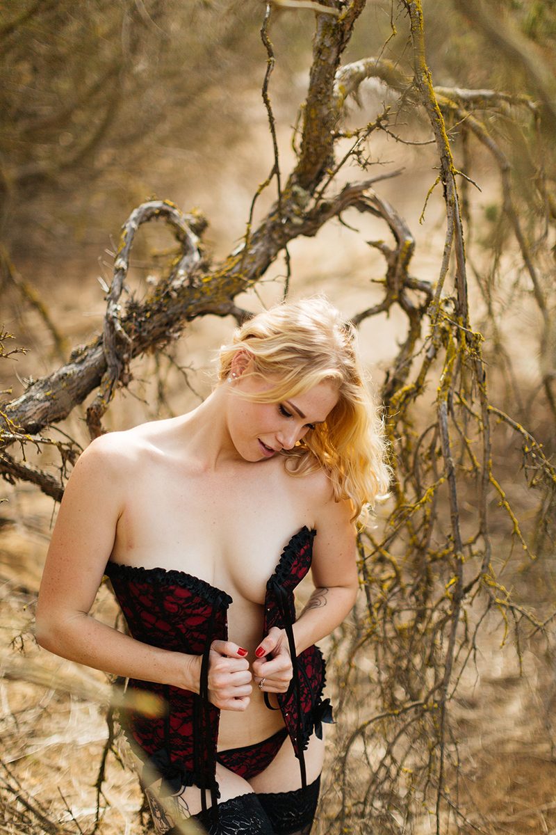 A beautiful young blonde woman poses for an Estelle Mountain Reserve boudoir photography session in a black and red corset with black underwear and stockings in a dry field in Corona just outside of Los Angeles, California
