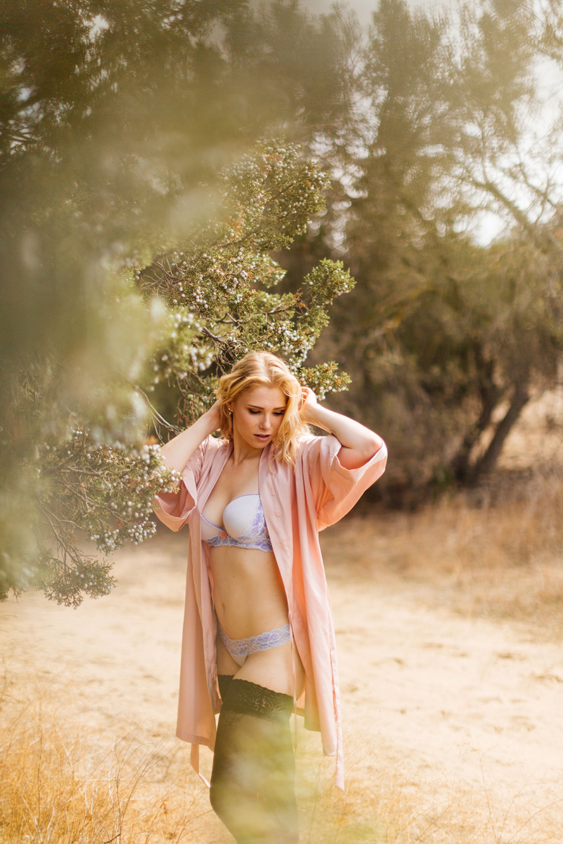 A beautiful young blonde woman poses for an Estelle Mountain Reserve boudoir photography session in a pink robe with a light blue bra and underwear with black stockings in a dry field in Corona just outside of Los Angeles, California
