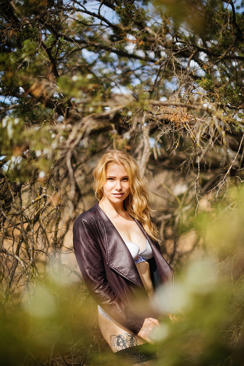 A beautiful young blonde woman poses for an Estelle Mountain Reserve boudoir photography session in a light blue bra and underwear with black stockings and a burgundy leather jacket in a dry field in Corona just outside of Los Angeles, California