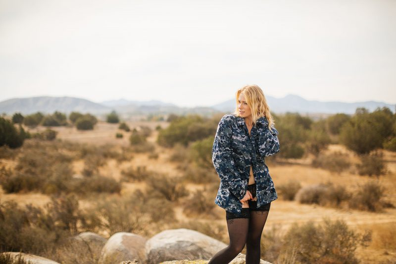 A beautiful young blonde woman poses for an Estelle Mountain Reserve boudoir photography session with black stockings, black and white bra, black underwear and a Navy digital BDU coat in a dry field in Corona just outside of Los Angeles, California