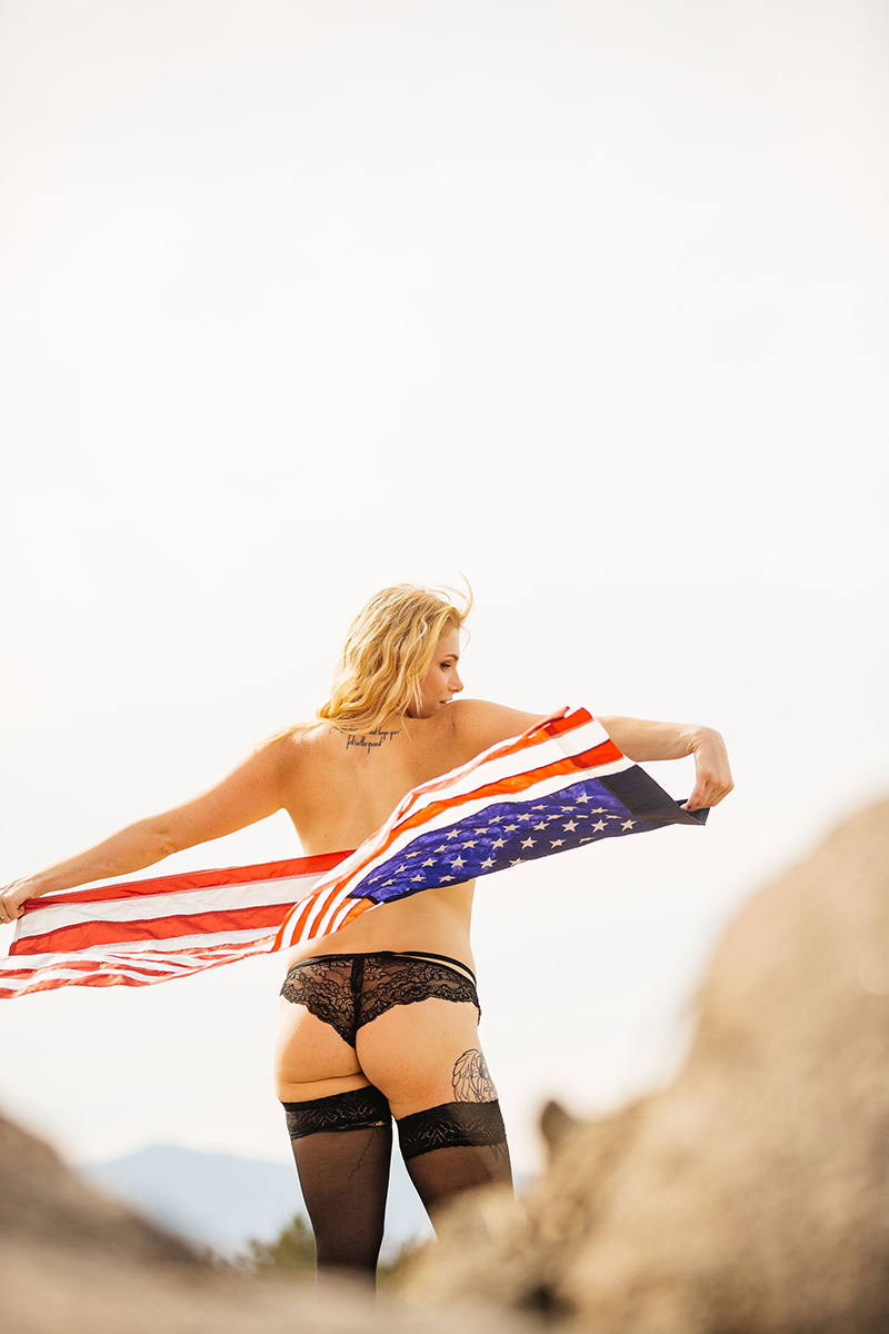 A beautiful young blonde woman poses topless for an Estelle Mountain Reserve boudoir photography session with black stockings and black underwear holding an American flag in a dry field in Corona just outside of Los Angeles, California
