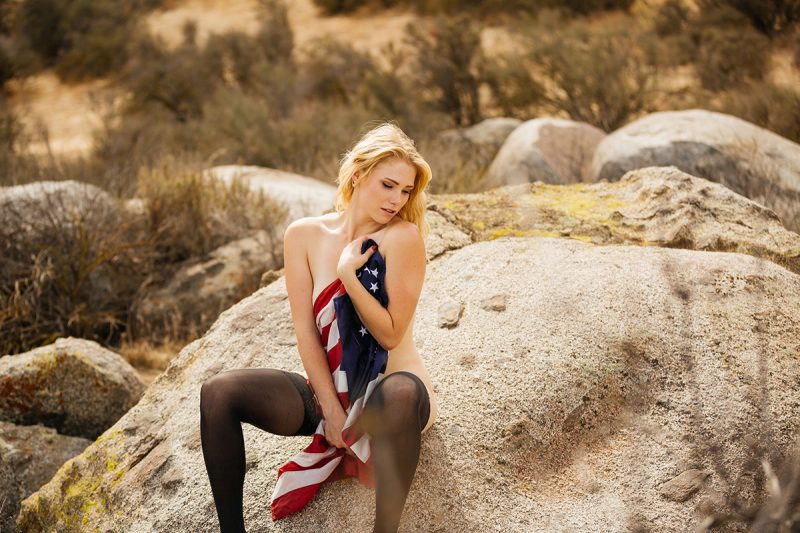 A beautiful young blonde woman poses nude for an Estelle Mountain Reserve boudoir photography session with black stockings wrapped in an American flag in a dry field in Corona just outside of Los Angeles, California