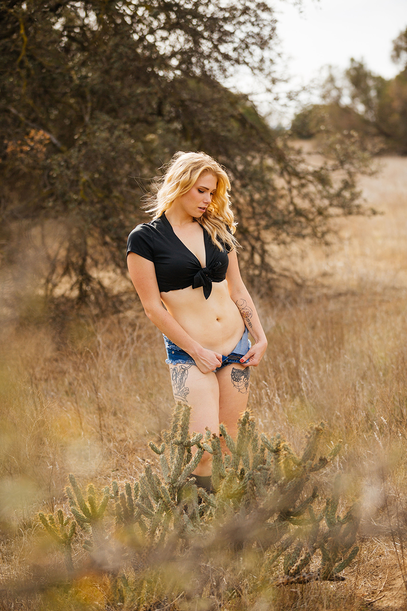 A beautiful young blonde woman poses for an Estelle Mountain Reserve boudoir photography session with black a black button up shirt and jean shorts in a dry field in Corona just outside of Los Angeles, California