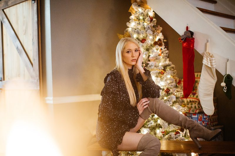 A young beautiful blonde woman poses for a Thornton Christmas boudoir photography session near Denver, Colorado wearing a black dress and tan boots sitting on a bench in front of a Christmas tree