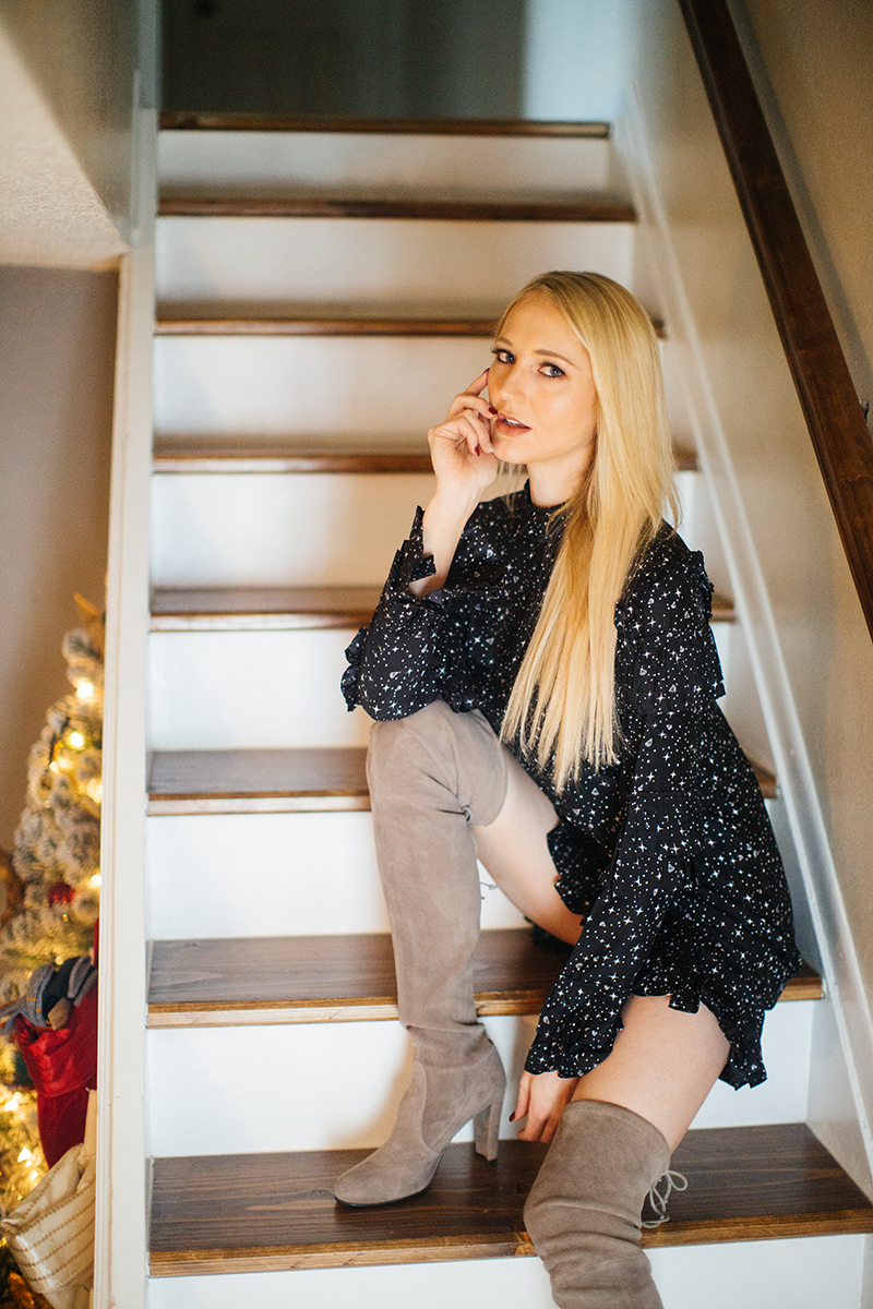 A young beautiful blonde woman poses for a Thornton Christmas boudoir photography session near Denver, Colorado wearing a black dress and tan boots sitting on stairs in front of a Christmas tree