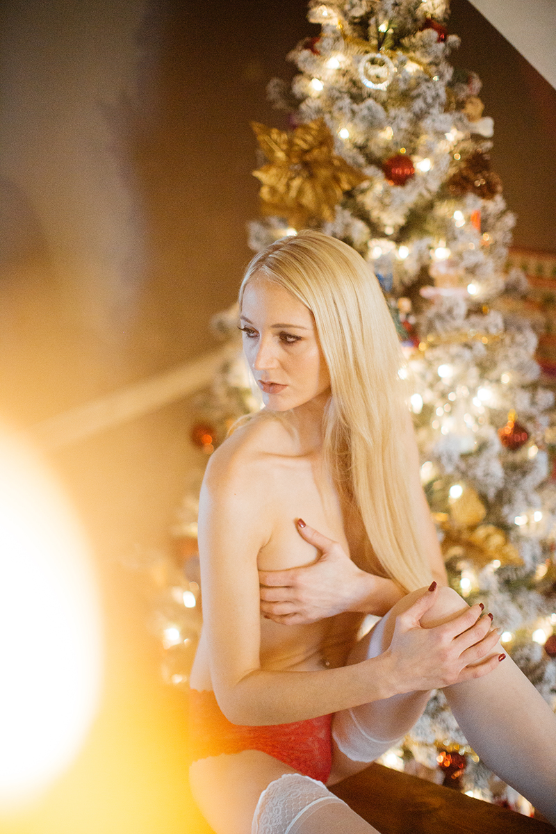 A young beautiful blonde woman poses topless for a Thornton Christmas boudoir photography session near Denver, Colorado wearing red underwear with white stockings sitting on a wood bench in front of a Christmas tree