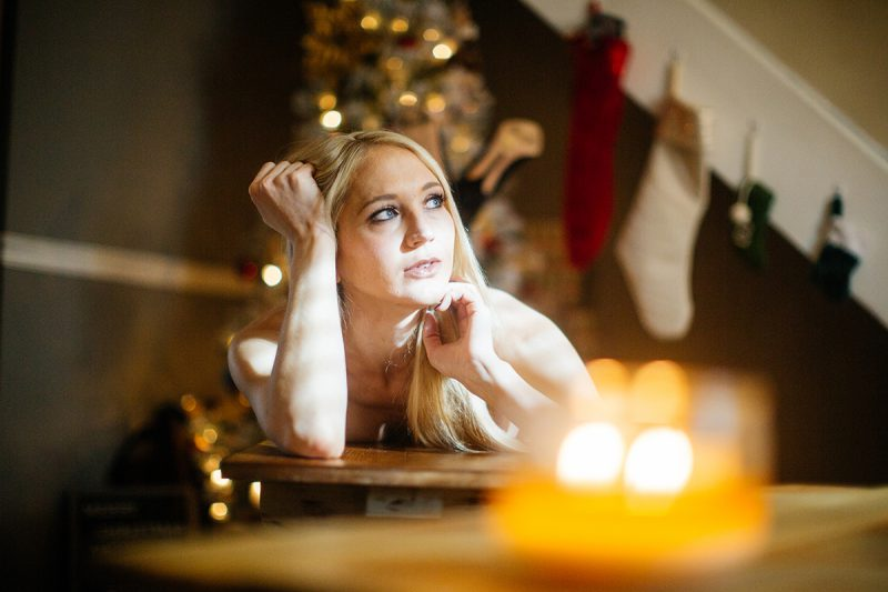 A young beautiful blonde woman poses topless for a Thornton Christmas boudoir photography session near Denver, Colorado wearing red underwear with white stockings laying on a wood bench in front of a Christmas tree