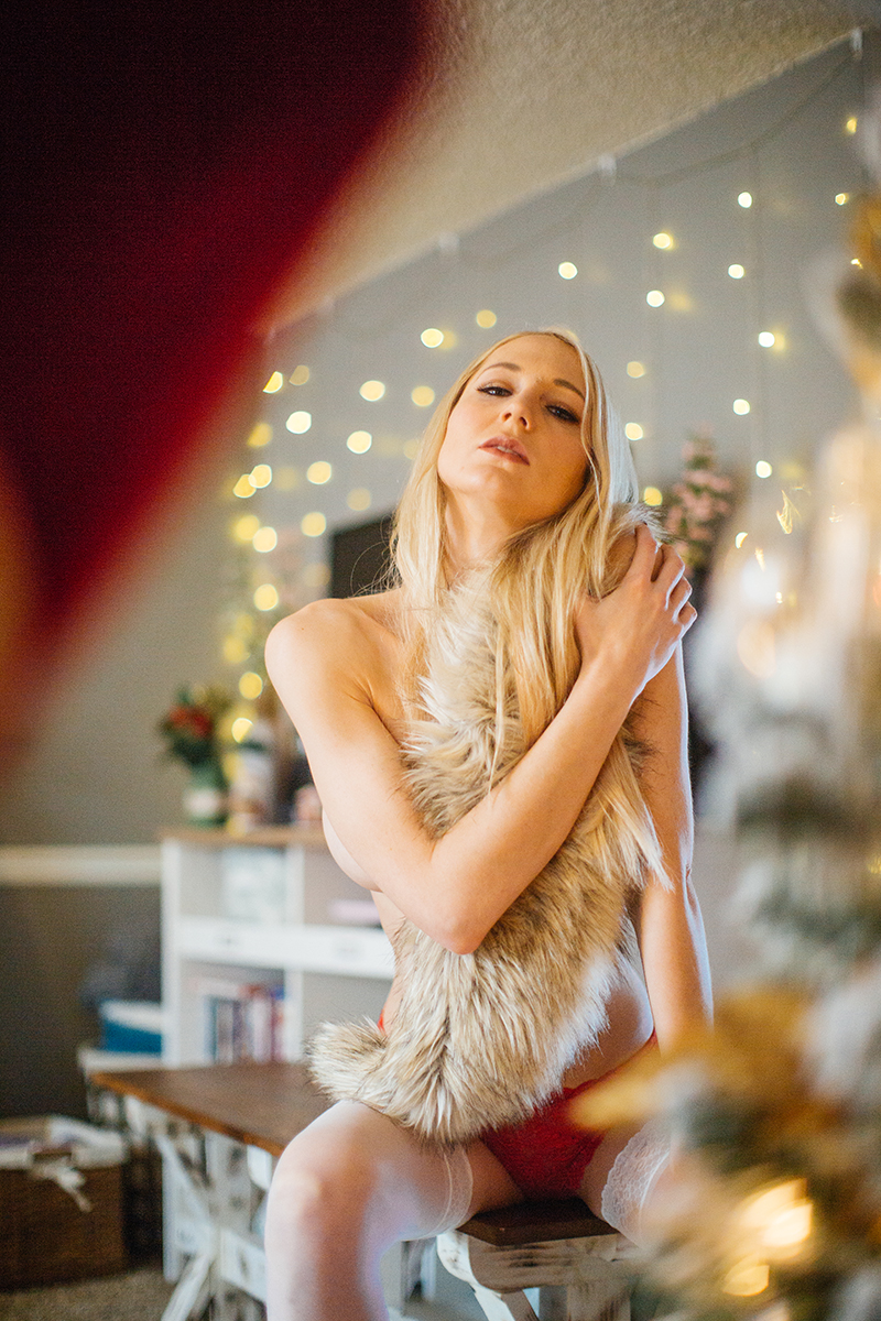 A young beautiful blonde woman poses topless for a Thornton Christmas boudoir photography session near Denver, Colorado wearing red underwear with white stockings and a fur while sitting on a wood bench in front of a Christmas tree
