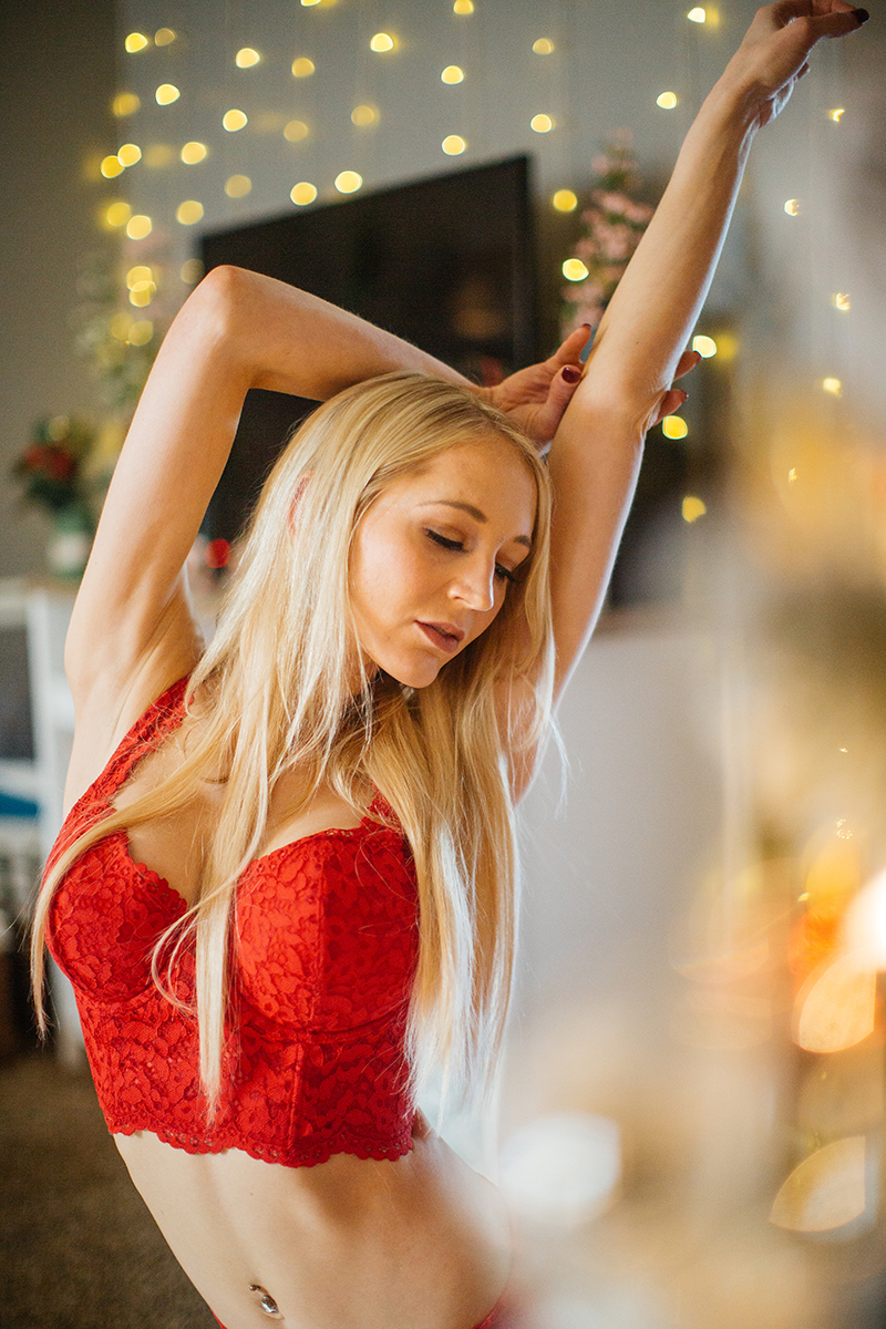 A young beautiful blonde woman poses for a Thornton Christmas boudoir photography session near Denver, Colorado wearing a red bra and red underwear lingerie set with white stockings while sitting on a wood bench near a Christmas tree