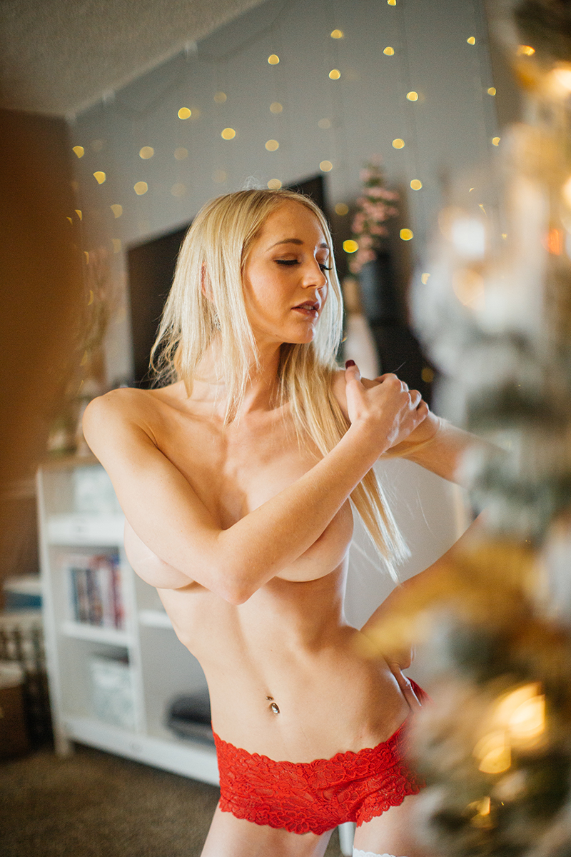 A young beautiful blonde woman poses topless for a Thornton Christmas boudoir photography session near Denver, Colorado wearing red underwear with white stockings while sitting on a wood bench near a Christmas tree