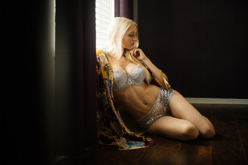A young beautiful blonde woman poses for a Thornton Christmas boudoir photography session near Denver, Colorado wearing a a light blue bra and sequin underwear with a floral robe sitting on a wood floor in front of a window