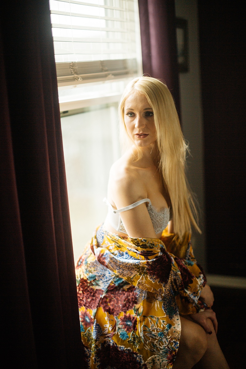 A young beautiful blonde woman poses for a Thornton Christmas boudoir photography session near Denver, Colorado wearing a light blue bra and sequin underwear with a floral robe sitting on the window ledge in front of a window