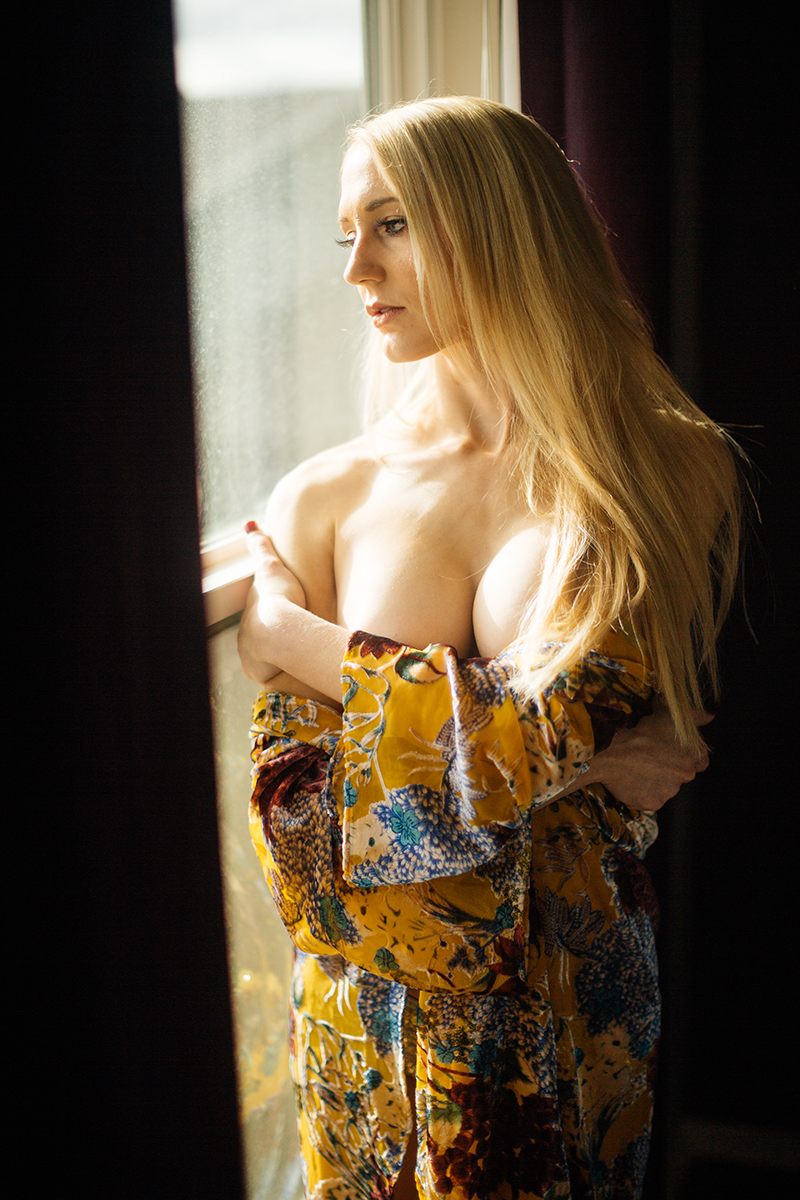A young beautiful blonde woman poses topless for a Thornton Christmas boudoir photography session near Denver, Colorado wearing a sequin underwear with a floral robe standing in front of a window