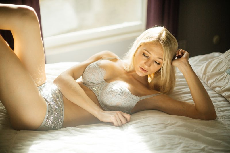A young beautiful blonde woman poses for a Thornton Christmas boudoir photography session near Denver, Colorado wearing a light blue bra and sequin underwear while laying on a white bed in front of a window
