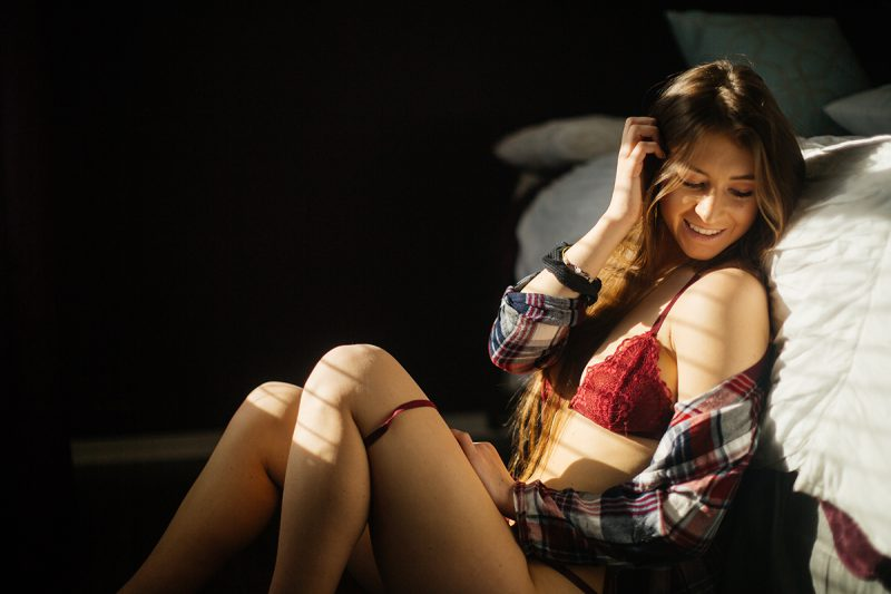 A beautiful young dirty blonde haired woman poses for a Thornton home boudoir studio photography session wearing a red strap bra and underwear set with a red plaid button up shirt sitting next to a white bed in front of a window near Denver, Colorado