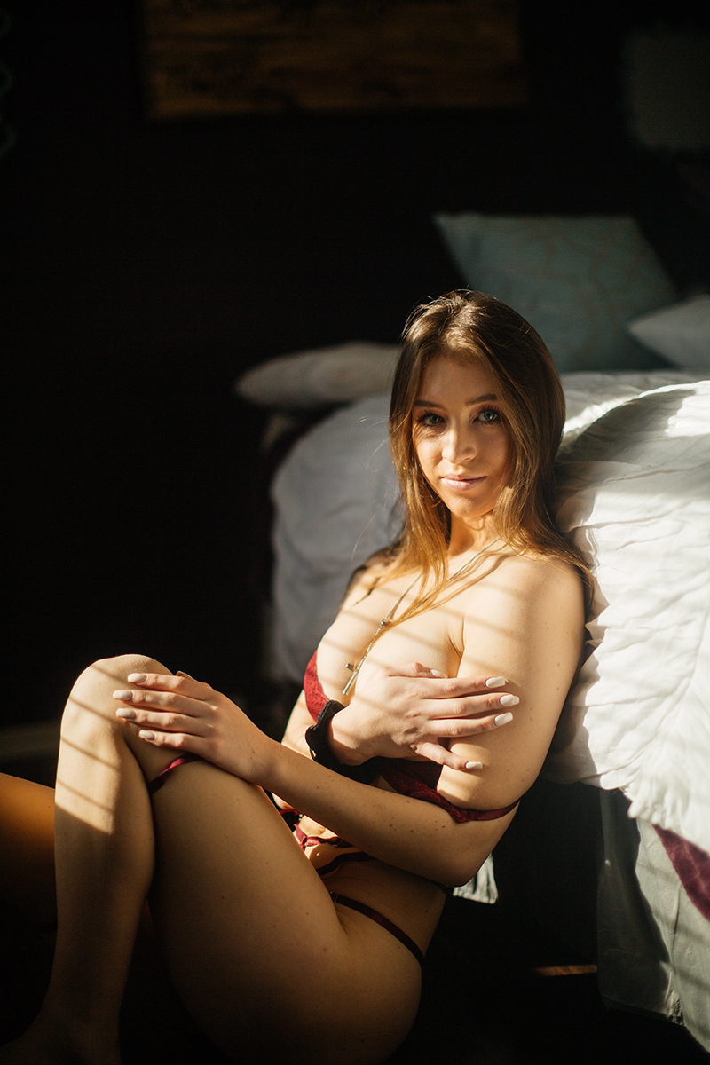 A beautiful young dirty blonde haired woman poses for a Thornton home boudoir studio photography session wearing a red strap bra and underwear set sitting next to a white bed in front of a window near Denver, Colorado