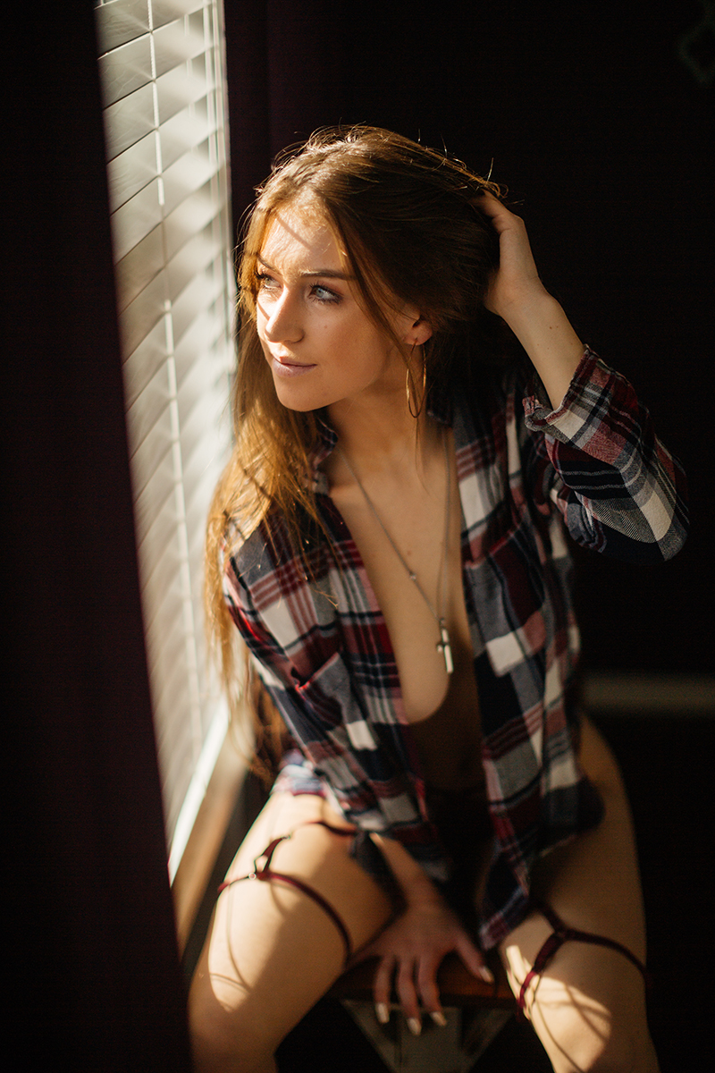 A beautiful young dirty blonde haired woman poses topless for a Thornton home boudoir studio photography session wearing red underwear and a red plaid button up shirt sitting on a wood bench in front of a window near Denver, Colorado