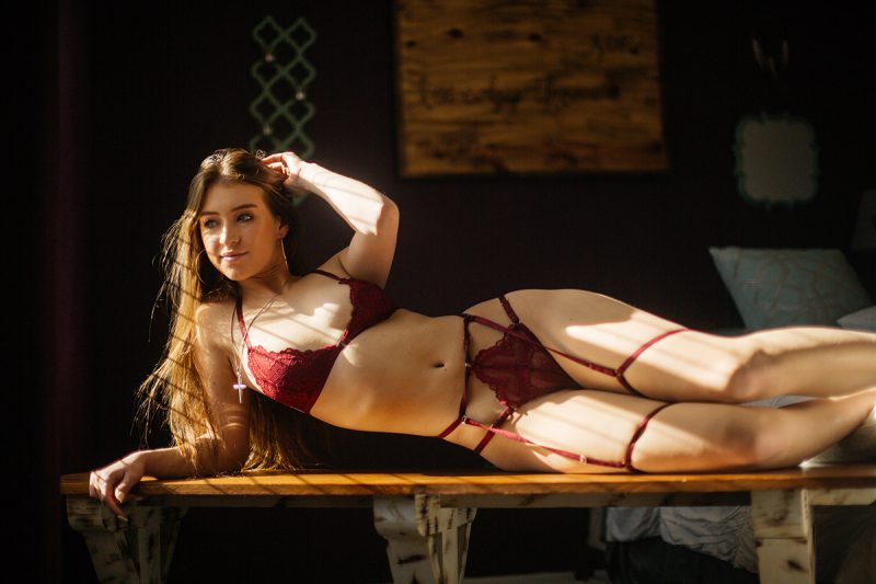 A beautiful young dirty blonde haired woman poses for a Thornton home boudoir studio photography session wearing a red strap bra and underwear set laying on a wood bench in front of a window near Denver, Colorado