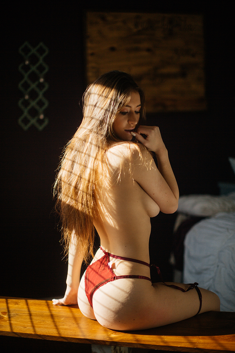 A beautiful young dirty blonde haired woman poses topless for a Thornton home boudoir studio photography session wearing red underwear sitting on a wood bench in front of a window near Denver, Colorado